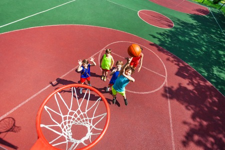 Kids standing on ground down and ball flying to the basket from top during basketball game