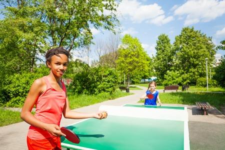 pingpong: Dos niñas jugando al ping pong al aire libre durante día soleado de verano Foto de archivo