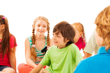 school age boy: Nice school age boy sit in the circle with friends smile and looking aside