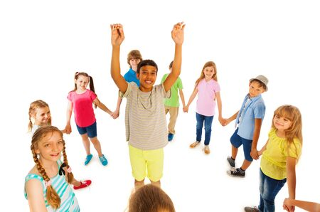 lifted hands: Group of kids boys and girls roundelay around nice boy with lifted hands Stock Photo