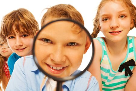 magnifying glass: Kid with looking through magnifier glass with close portrait of boy through the lens smile and curious