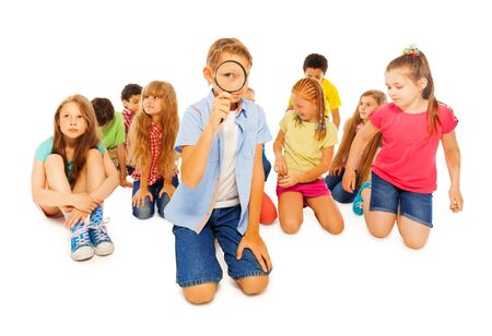 sit around: Group of friends diverse school children sit together around boy with magnifying glass