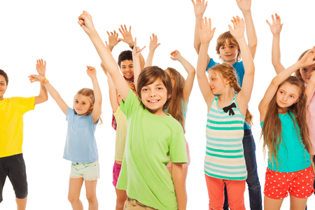 lifting hands: Group of happy kids standing and lifting hands in the air happily smiling isolated on white
