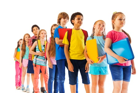 Group of school kids with diverse appearance standing in the line holding textbooks and folders
