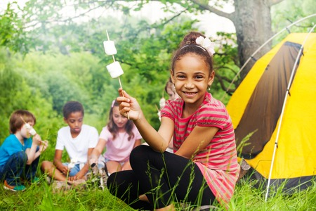 Happy African girl holding stick with marshmallow treat during camping in the forest with other kids