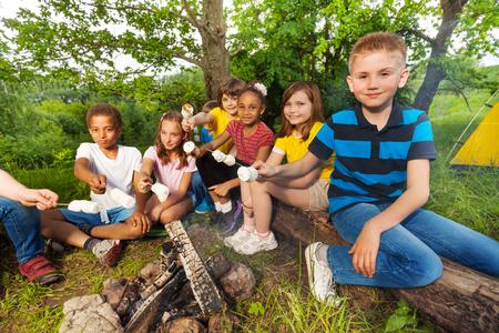 campamento: Grupo de niños sentados cerca de la hoguera con bastones de malvavisco durante acampar en el bosque junto