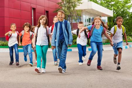 дети: Дети с рюкзаки рядом здании школы ходьбе, держась за руки в летнее время дня