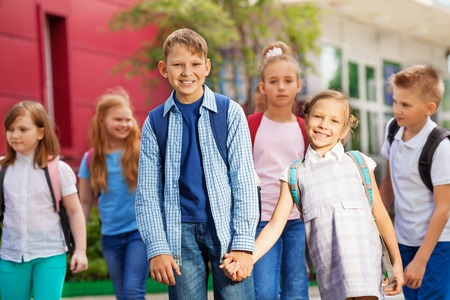 rucksacks: Group of happy kids with rucksacks near school facade building walking holding hands during summer day time Stock Photo