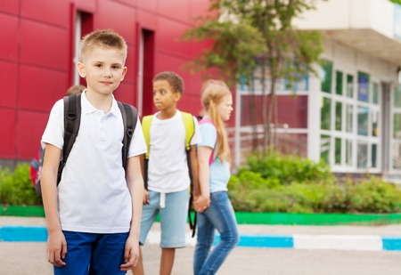 elementary: Three kids with rucksacks near school building  facade walking holding hands during summer day time