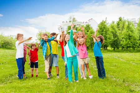 Happy kids reach after white airplane toy with arms standing close in the field during summer day