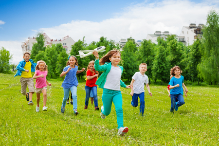 Running girl holding big white airplane toy and children behind in the field  in colorful clothes during summer day Stock Photo