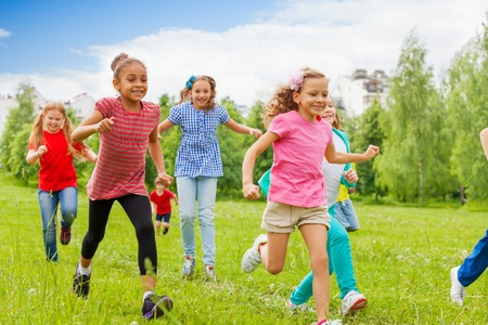 Group of happy kids running through the green field together during summer day