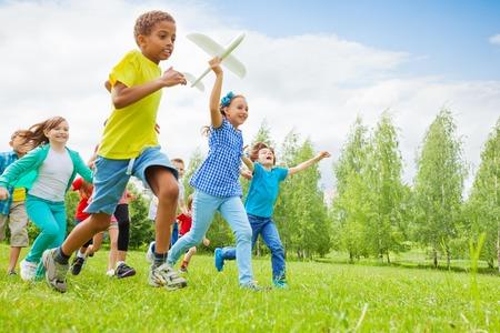 Niña feliz celebración de avión de juguete y los niños detrás de correr en el campo durante el día de verano