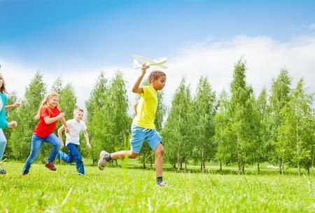 Afrikaanse jongen die groot wit vliegtuigstuk speelgoed en kinderen achterlaten die tijdens de zomerdag in het veld loopt Stockfoto