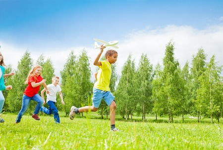 African boy holding big white airplane toy and children behind running in the field during summer day