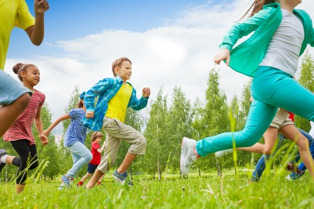 Running children view in the green field together during summer day