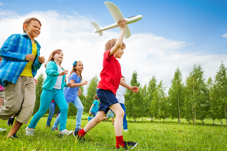 Small boy holds white airplane toy and kids behind running in the field during summer day Imagens