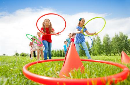 カラフルなフープで遊ぶ子供たちの 2 つグループ夏の晴れた日の間にお互いに競争しながら円錐形にそれらを投げると