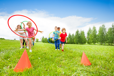 multiple targets: Playful kids throwing colorful hoops on cones while competing with each other during summer sunny day Stock Photo