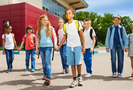 rucksacks: Children holding hands carry rucksacks and walk near school building during summer day time Stock Photo