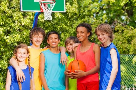 niños en recreo: Amigos internacionales colocan en una fila después de partido de baloncesto al aire libre durante el día soleado de verano Foto de archivo