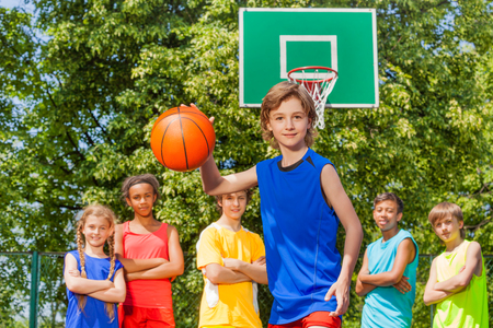 international basketball: Boy plays basketball with international team behind standing outside during sunny summer day