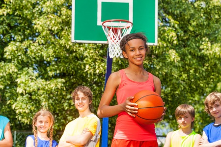 international basketball: Smiling African girl with ball and international friends standing behind at basketball game outside during sunny summer day