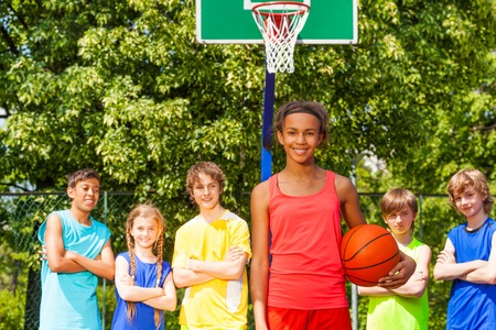 playground basketball: Smiling African girl with ball and her team  standing behind at basketball game outside during sunny summer day Stock Photo