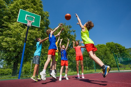 playground basketball: Teens in jump playing basketball game together on the playground during sunny summer day
