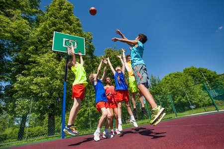 Jumping for ball teenagers playing basketball game together on the playground during sunny summer day Foto de archivo