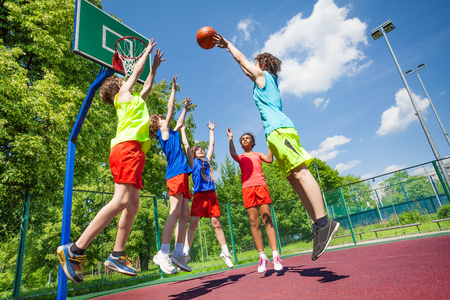Children jump for ball during basketball game on the ground at sunny summer day together
