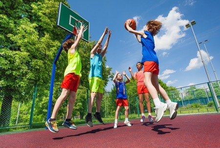 boy basketball: Teens jump for ball during basketball game on the ground at sunny summer day together Stock Photo