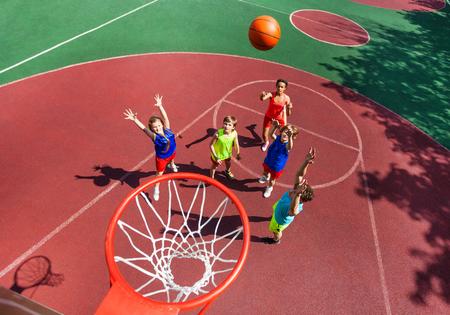 바닥에 서있는 아이들과 농구 경기 중 바구니 가기 볼에 비행 공