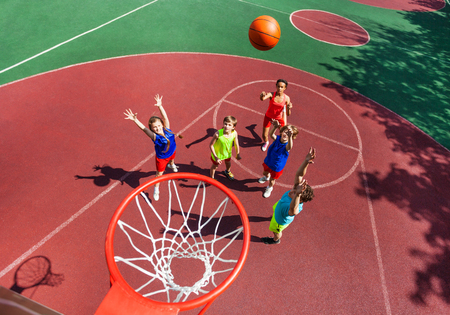 Fliegen Ball in den Korb Draufsicht während der Basketball-Spiel mit Kindern stehen auf dem Boden nach unten Standard-Bild