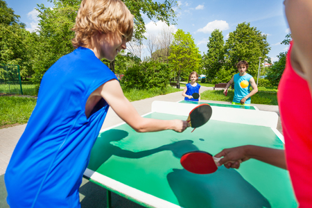 Four international friends playing table tennis outside during summer sunny day