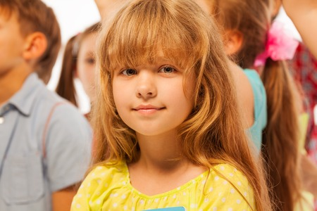 niños en la escuela: Nice little girl stand in the large group of friends and mates, close-up portrait Foto de archivo