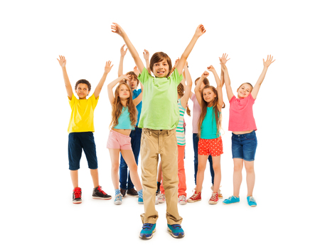 lifted hands: Happy boys and girls stand together with lifted hands raised in the air in large group Stock Photo