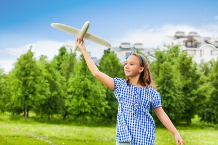 child model: Happy girl holds airplane toy with straight arm in the green field during summer sunny day