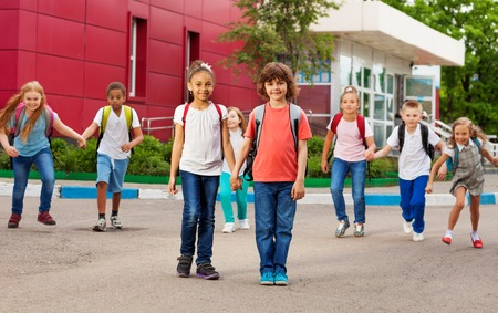 elementary: Rows of kids with rucksacks near school walking holding hands during summer day time Stock Photo
