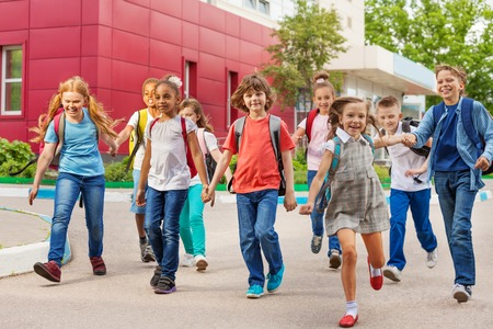 Happy kids with rucksacks walking holding hands near school building during summer day time Archivio Fotografico