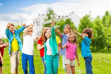 bewegung menschen: Girl holding big white airplane toy and children behind catching her in the field during summer day