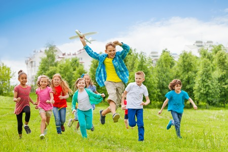 large group of people: Jumping boy holding big white airplane toy and children behind running in the field during summer day