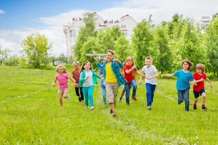 correr: El muchacho sostiene avión de juguete blanca grande y los niños detrás corriendo en el campo durante el día de verano