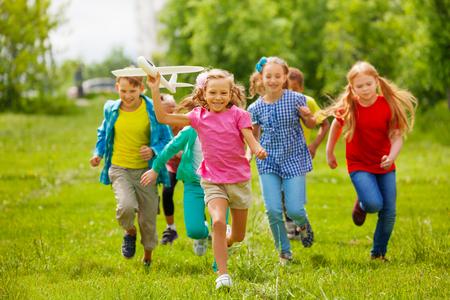 ropa de verano: Vista de la niña de la celebración de avión de juguete grande y los niños en ropa de colores detrás corriendo en el campo durante el día de verano