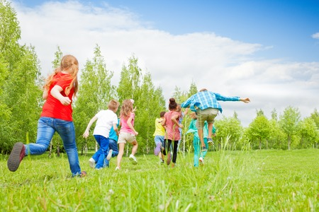 View from behind of happy kids running through the green field together during summer day