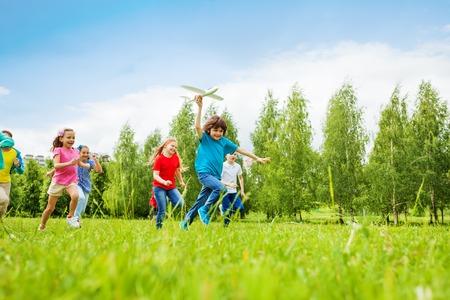 niños felices: Vista de rápido movimiento niño de la celebración de avión de juguete blanco grande y los niños detrás corriendo en el campo durante el día de verano Foto de archivo