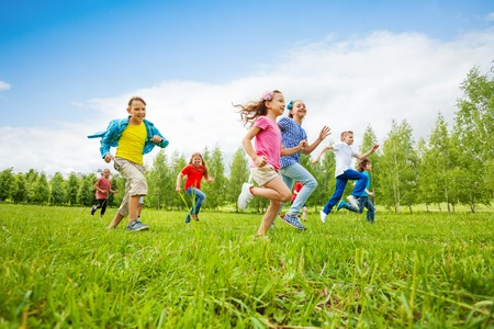 sport team: Children are running through the green field together during summer day
