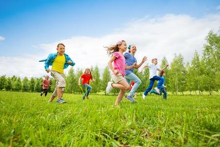 ni�os sonriendo: Los ni�os se est�n ejecutando a trav�s del campo verde juntos durante el d�a de verano Foto de archivo