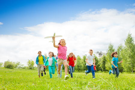 green field: Small girl holding big white airplane toy and kids behind running in the field during summer day