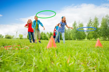 夏の晴れた日の間にお互いに競争しながら円錐形のカラフルなフープを投げて遊ぶの子供たちの 2 つのグループ